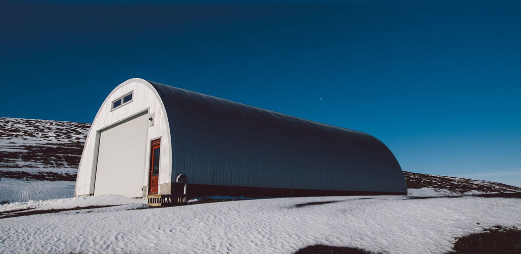 Built structure on snow covered land against clear blue sky