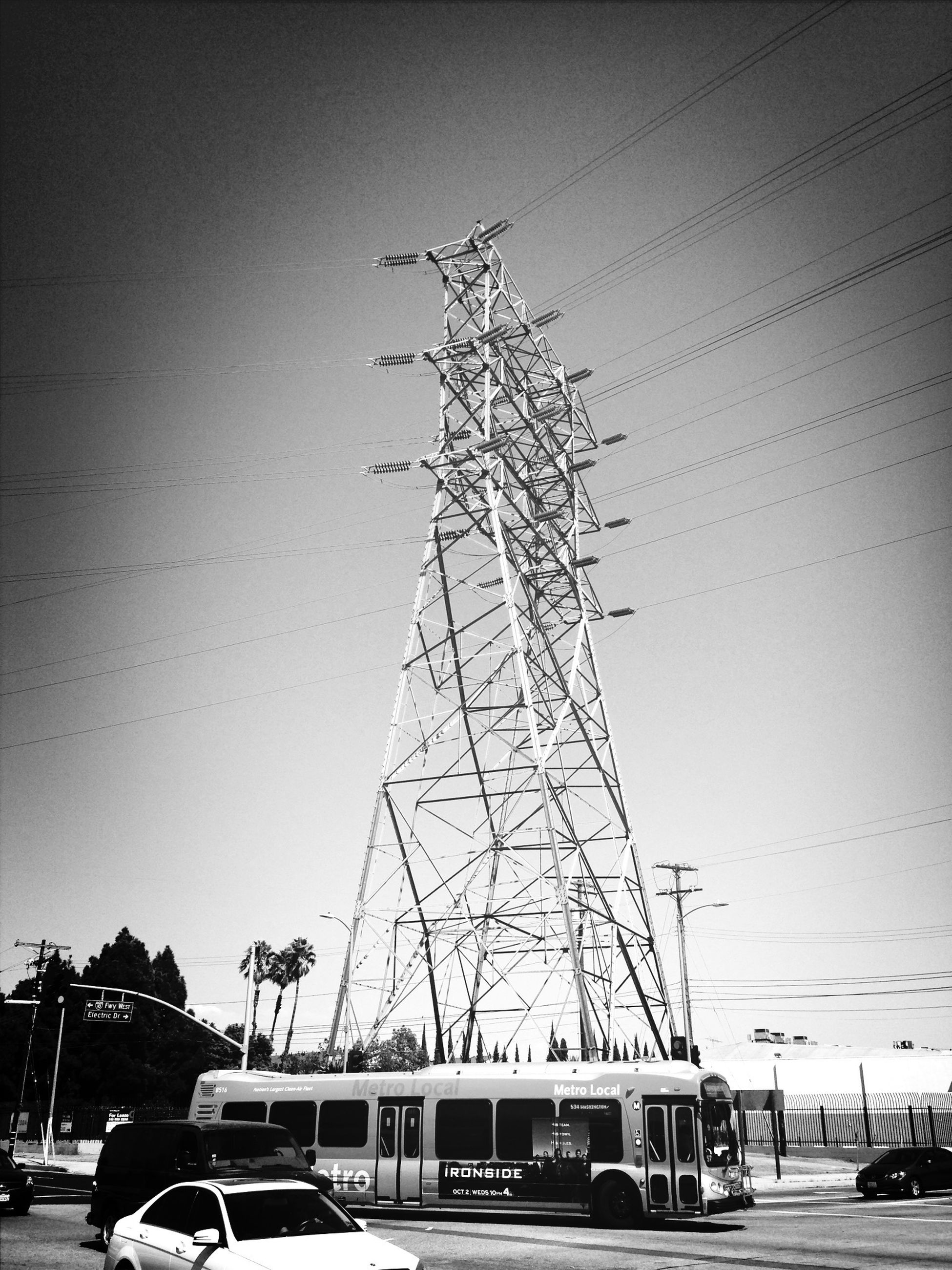 transportation, mode of transport, car, land vehicle, power line, electricity pylon, clear sky, road, electricity, sky, low angle view, street, power supply, fuel and power generation, technology, connection, cable, travel, outdoors, no people