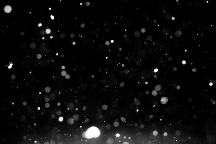 Defocused image of illuminated lights against sky at night