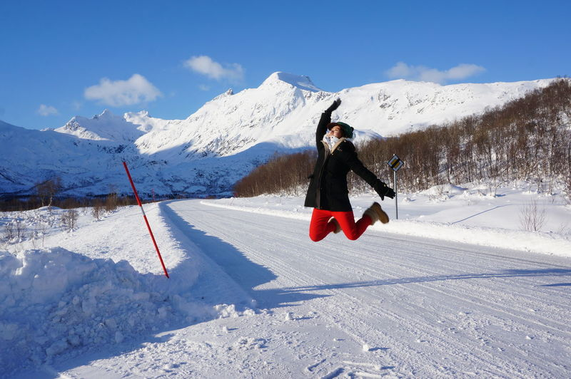 Full Length Of Woman Jumping On Snow Covered Landscape