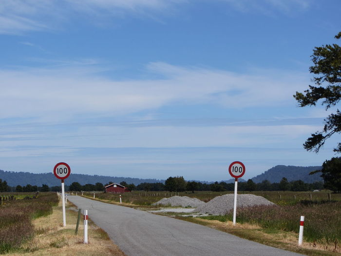 Signs along road against blue sky