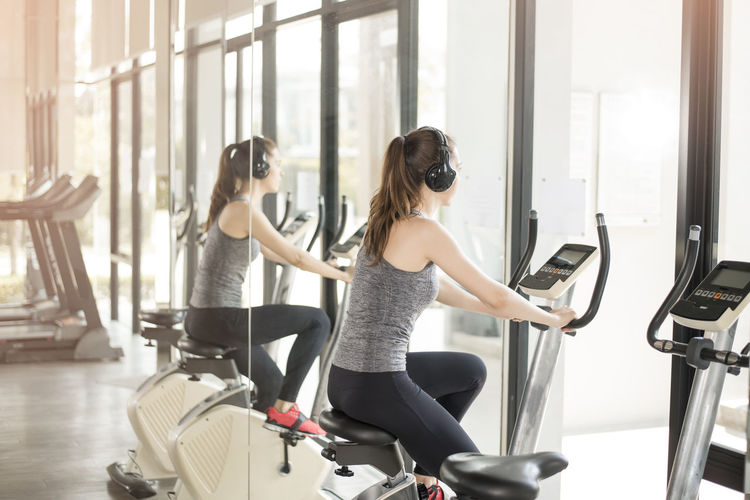 Side view of young woman listening music while exercising on equipment at gym with reflection in mirror