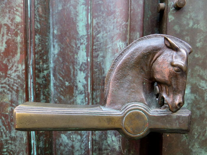 Close-up of horse shaped handle on door