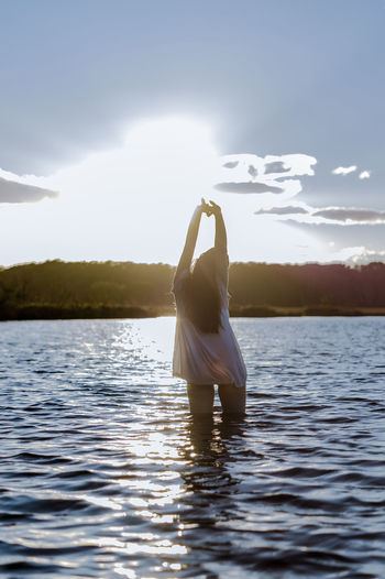 Adult Arms Raised Beauty In Nature Day Hand Human Arm Lake Leisure Activity Lifestyles Nature One Person Outdoors Real People Rear View Scenics - Nature Sky Standing Sunlight Tranquil Scene Tranquility Water Waterfront Women