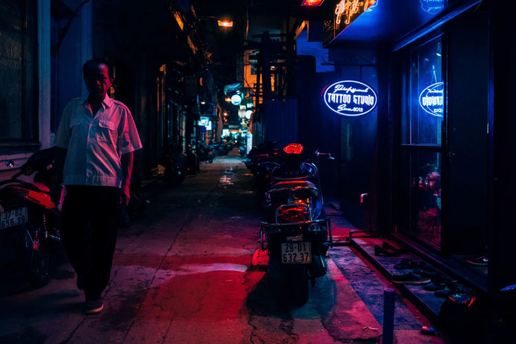 Full length of woman walking on illuminated city at night