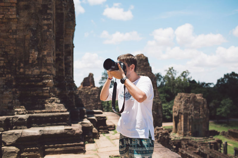 Mid Adult Man Photographing With Digital Camera At Ankor Wat Temple
