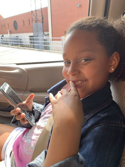 Portrait of smiling girl using mobile phone
