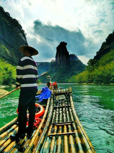 Man standing on wooden raft against rock cliffs and clouds