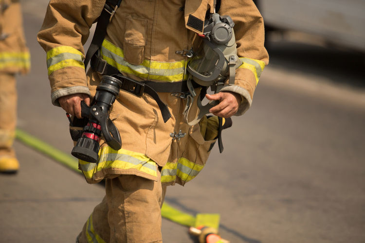 Midsection of firefighter on street