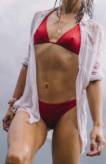 Midsection of wet woman wearing bikini against sky