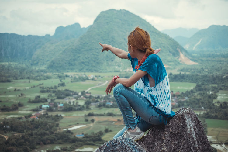 Side view of mid adult woman pointing at mountains while sitting on cliff