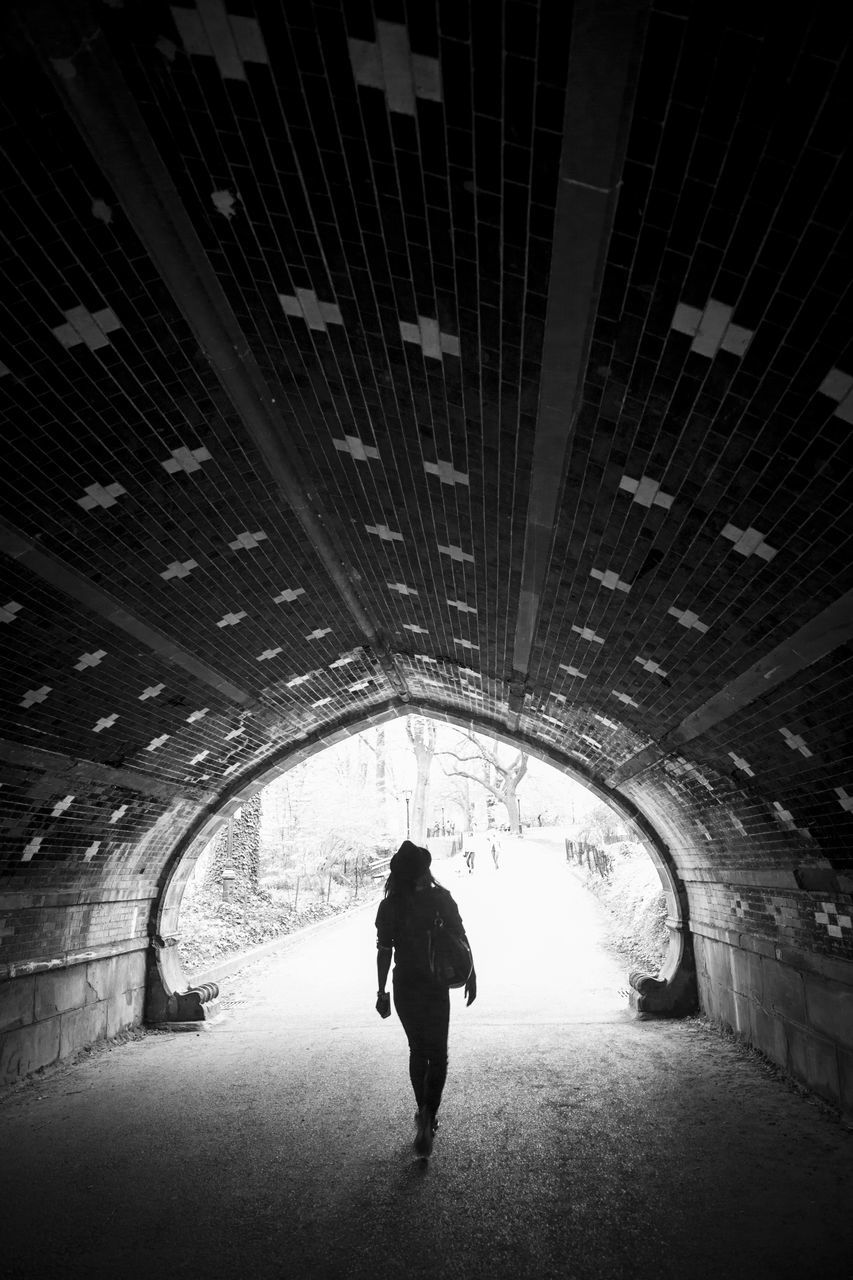 walking, real people, architecture, built structure, silhouette, rear view, one person, the way forward, indoors, tunnel, arch, full length, leisure activity, lifestyles, men, illuminated, standing, day, people