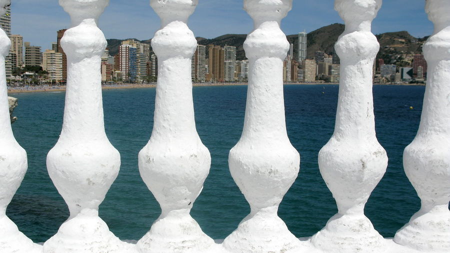 View of sea against city seen through baluster