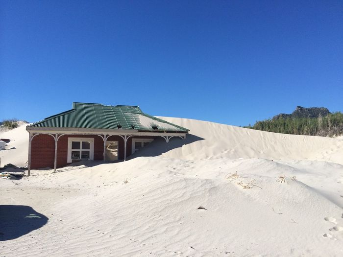 Exterior Of House Covered With Sand Against Blue Sky