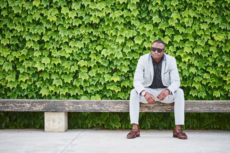 Full length of young man sitting on bench