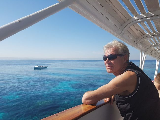 Male Senior Model watching Coral Reef in Crystal Blue Red Sea against Blue Sky from Board of Boat...... EyeEm Selects Sea Man One Man Only One Person Adults Only Sunglasses Mid Adult Water Adult Vacations Travel Leisure Activity Day People Sky Travel Destinations No Edit/no Filter Yachting Adults Only Adult White Boat Blue Blue Sea Horizon Over Water Boat Tour This Is Aging