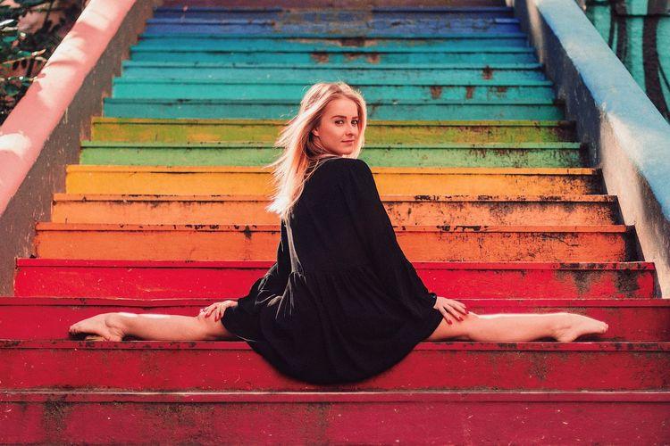 Beautiful female fashion dancer in urban colorful staircase