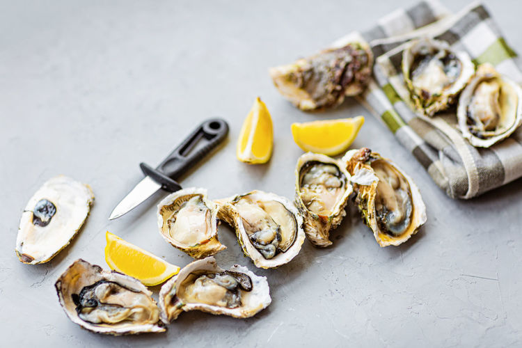 Fresh oysters and lemon on gray concrete background
