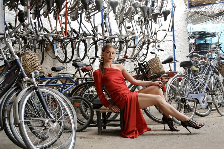 Full length portrait of woman in red elegant drsitting on bicycle surrounded by hundreds of bicycles