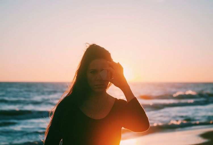 Portrait of woman on beach against sky during sunset