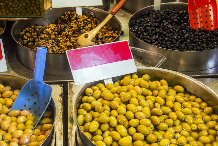 Bowls of olives for sale at a market Abundance Bowls Business Choice Collection Consumerism Food Food And Drink For Sale Freshness Healthy Eating Market Market Market Stall Olives Pineapple Price Tag Retail  Retail Display Sale Sale Selling Small Business Variation Vegetable