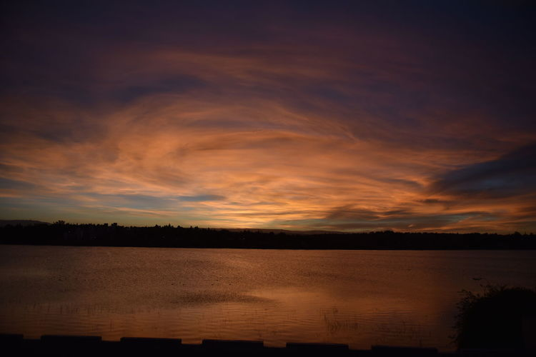 Scenic view of lake against romantic sky during sunset
