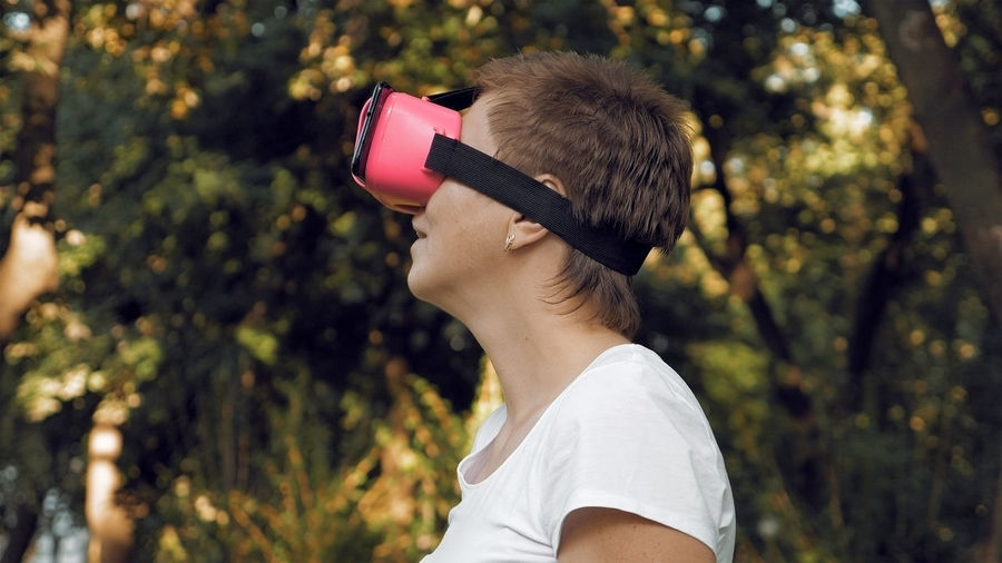 Side view of woman using virtual reality simulator against trees