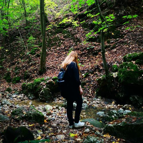 Rear view of woman walking in forest