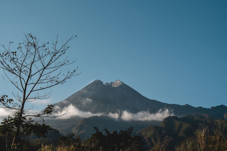 Mount merapi with a blue sky background is located in yogyakarta, indonesia