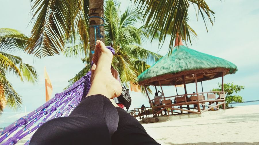 Rest and Relaxation Beach Vacations Sand Palm Tree Tropical Climate Only Women Hammock Adults Only Relaxation Sea Adult One Woman Only Travel One Person People Day Enjoyment Barefoot Tree Human Body Part Eye Em Philippines MomentsToRemember Travel Destinations