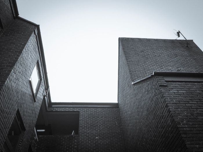 Architecture Built Structure Building Exterior Low Angle View Clear Sky No People City Day Outdoors Streetphotography Street Residential Building Urban Landscape Point Of View London Blackandwhite Photography Blackandwhite IPhoneography Daylight Satalite Dish Brick Wall Window Shadow