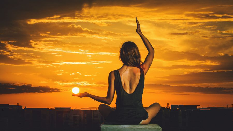 Optical illusion of woman holding sun while performing yoga at building terrace