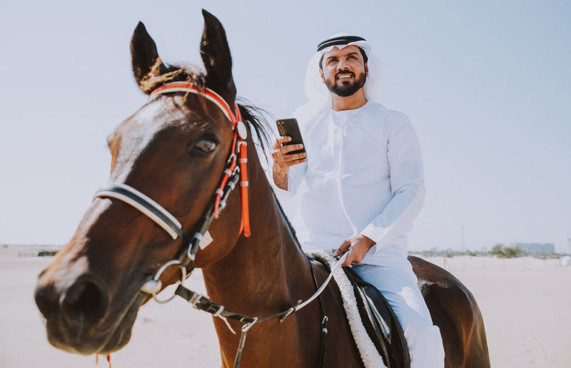 Young man with mobile phone riding horse at desert