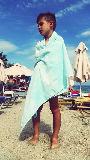 Full length of boy covered with towel standing at beach