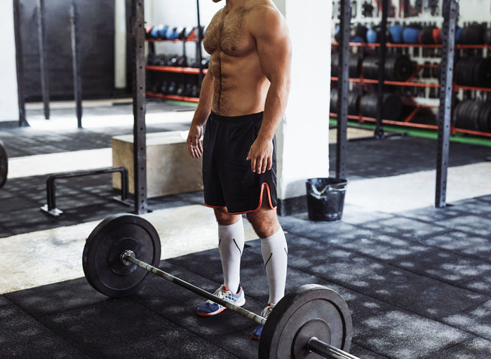 Low Section Of Shirtless Man Standing By Barbell In Gym