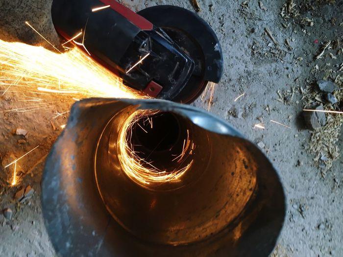 Circular saw cutting metallic pipe at workshop