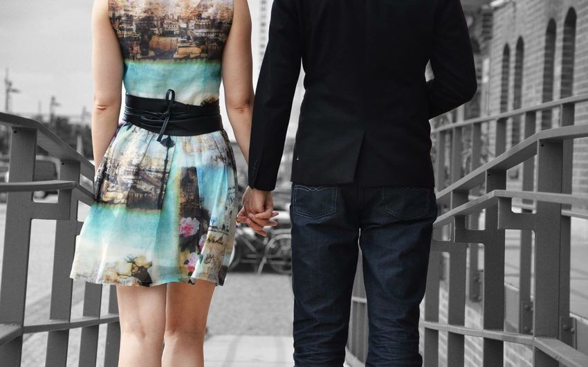 Midsection of couple walking amidst railings in city
