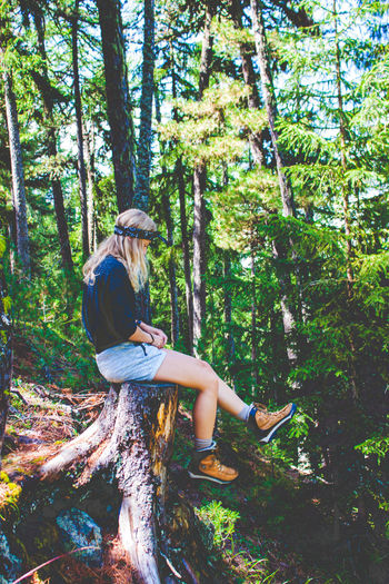 Side view of woman sitting on tree stump in forest