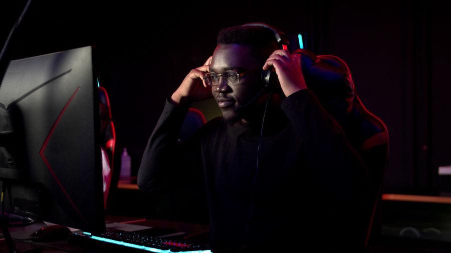 Man playing video game in darkroom