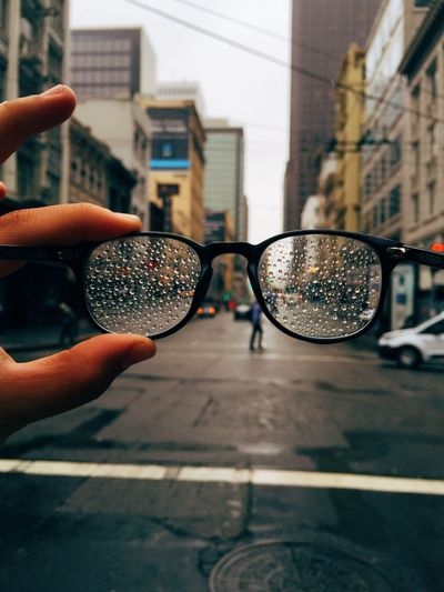 Cropped image of hand holding wet eyeglasses against city street