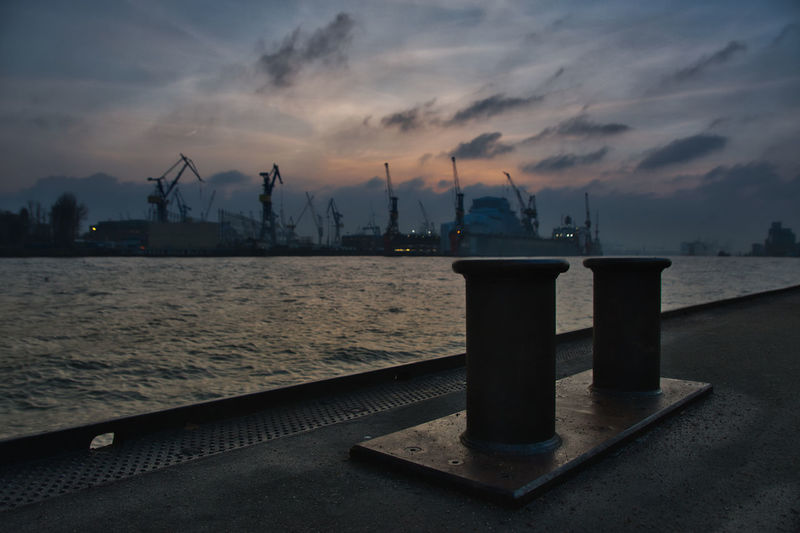 Commercial dock by sea against sky at sunset