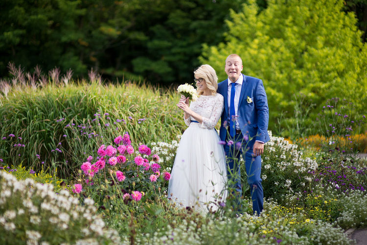 Groom making face while bride holding bouquet while standing amidst plants at park