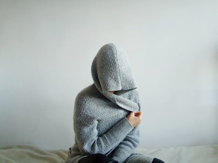 Person wearing warm clothing sitting on bed against wall