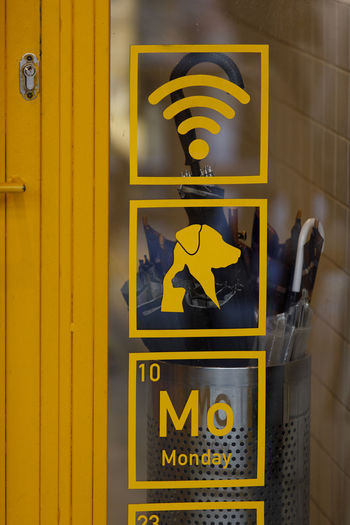 Cafe Animal Themes Animals Cat Dog Communication Yellow Sign Text Guidance Western Script No People Symbol Direction Representation Directional Sign Information Sign Human Representation Information Illuminated Arrow Symbol Day Close-up Outdoors Pedestrian Crossing Sign