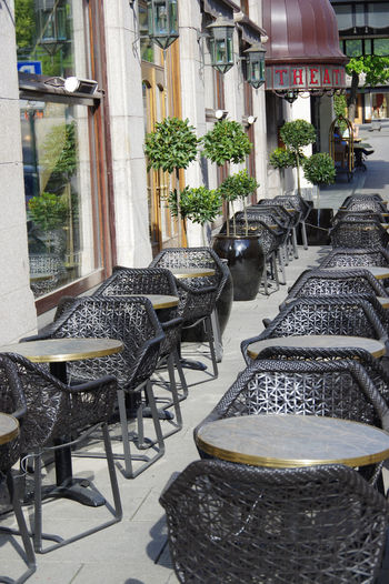 Empty chairs and tables at sidewalk cafe amidst buildings