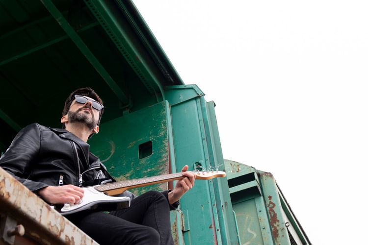 Low angle view of man playing guitar sitting in train