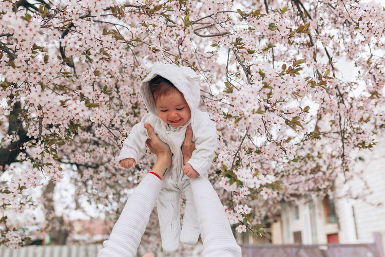 Happy Cute Girl Held By Cropped Mother Against Cherry Blossoms