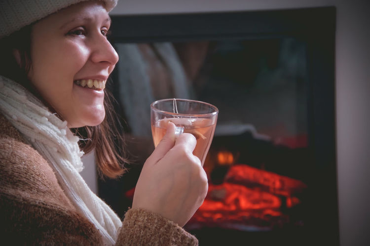 Side view of smiling woman holding tea cup while sitting by fireplace at home