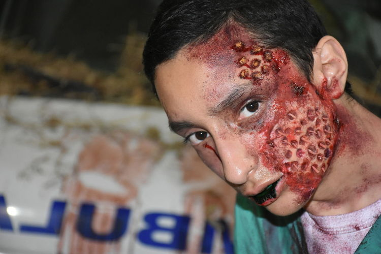Close-up portrait of teenager boy with zombie face during halloween