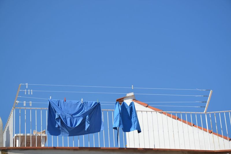 Low angle view of blue fabrics drying on clothesline
